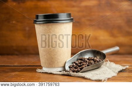 Disposable take-out mockup paper cups with coffee beans for morning espresso and spoon in brown bowl on wooden background