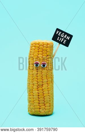 a corncob with eyes standing on a blue background holding a black sign that reads vegan life