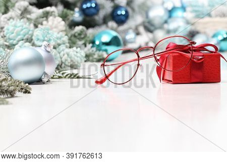 Christmas Eyeglasses Red Spectacles Near Package With Ribbon Bow Isolated On White Table With Balls
