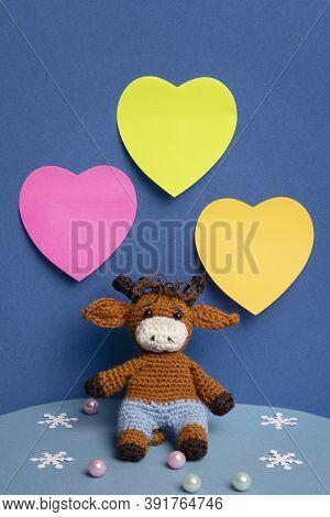 Hand-knitted Goby Toy On A Blue Background. Space For Writing In The Form Of Multi-colored Hearts