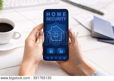 Home Automation, Remote Control. Over The Shoulder View Of Woman Using Her Mobile Phone With House S