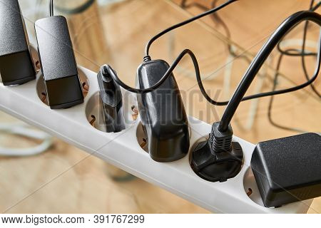 Electrical Power Strip Overloaded With Multiple Electrical Cords Plugged In. Many Plugs Plugged Into