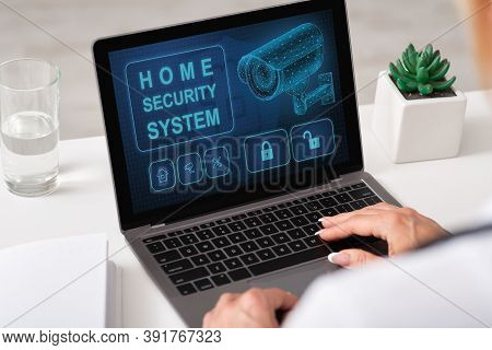 Smart House, Home Automation. Over The Shoulder View Of Woman Using Laptop With Home Security System