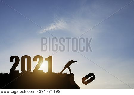 Man Push Number Zero Down The Cliff Where Has The Number 2021 With Blue Sky And Sunrise. It Is Symbo
