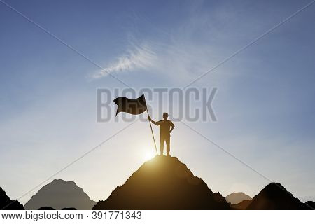 Silhouette Of Businessman Holding Flag On The Top Of Mountain With Over Blue Sky And Sunlight. It Is