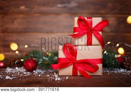Christmas Greeting Card Concept. Gift Box With Christmas Tree And Lights On Wooden Background. Copy