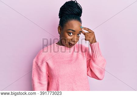 Young african american woman wearing casual winter sweater pointing unhappy to pimple on forehead, ugly infection of blackhead. acne and skin problem