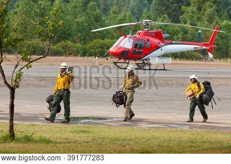 Prospect,  Oregon / Usa - September 13, 2014:  Three Fire Crew Members Walk Across The Runway With T