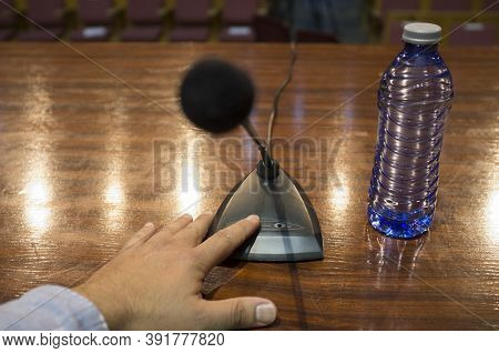 Speaker Finger Is About To Press On-off Button Of A Table Conference Microphone. Selective Focus