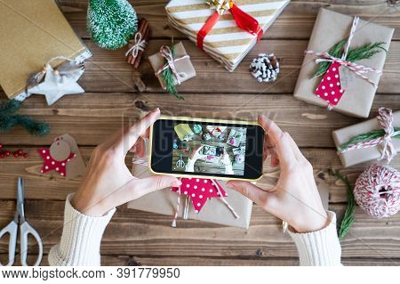 Flat Lay Of Woman S Hands Wrapping Christmas Gift And Taking Pictures On The Phone. Unprepared Prese