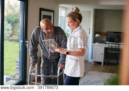 Senior Man In Dressing Gown Using Walking Frame Being Helped By Female Nurse With Digital Tablet