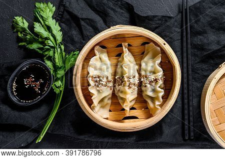 Japanese Gyoza In A Traditional Bamboo Steamer. Top View. Rustic Old Vintage Black Background