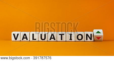 Valuation Word On Wooden Cubes, Up And Down Signs On Orange Background. Business Concept, Copy Space