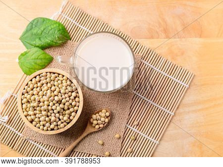 Soy Milk In The Glass And Soy Beans On Wooden Background, Top View
