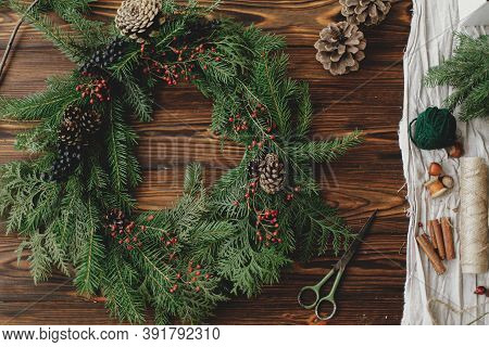 Rustic Christmas Wreath On Wooden Table Flat Lay. Holiday Workshop
