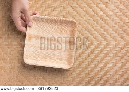 Hand Holding Betel Palm Leaf Plate (biodegradable, Compostable Or Eco Friendly Disposable Plate) On