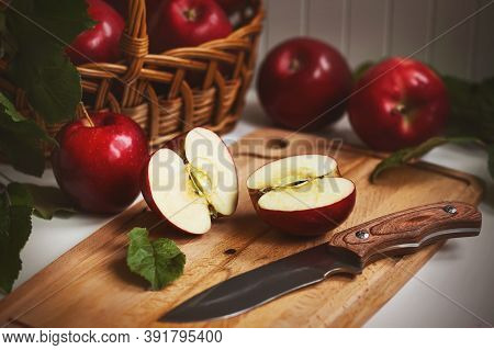 On The Kitchen Table Still Life - Wicker Basket With Red Ripe Sweet Apples, Next To It A Wooden Boar