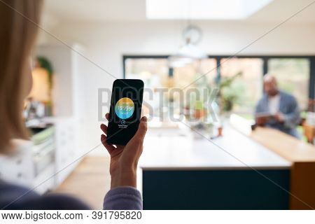 Mature Woman Using App On Phone To Control Digital Central Heating Thermostat At Home
