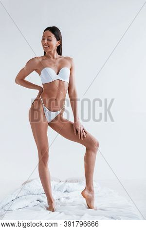 Young Woman In Underwear And With Nice Body Shape Is Posing In The Studio Against White Background.
