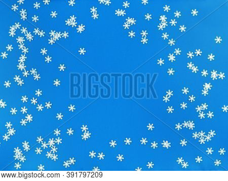 Scattered White Snowflakes On A Blue Background. Simple Flat Lay With Copy Space. Stock Photo.