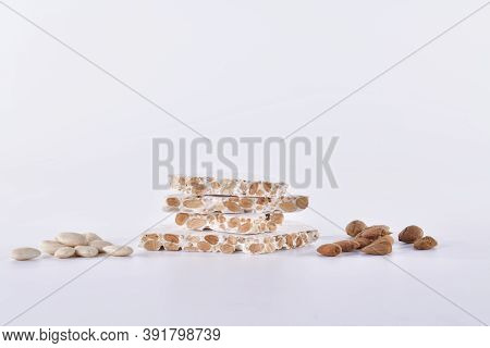 Delicious Looking Blocks Of Almond Nougat Surrounded By Peeled And Unpeeled Almonds On Alight Backgr