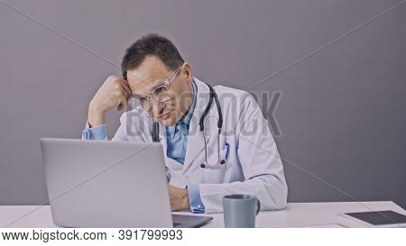 Handsome Male Doctor In White Uniform Working On Computer Takes A Sip Of Coffee Tired Of Work Sittin