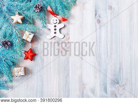 Christmas background. New Year and Christmas background. Christmas toys, blue fir tree branches on the rustic wooden background. New Year and Christmas still life, free space for text. Christmas card, Christmas festive border