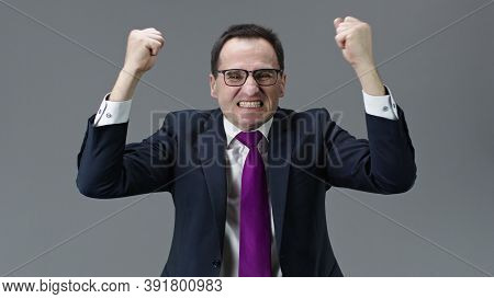 Furious, Angry Middle Aged Businessman In Formal Clothes, Tie And Glasses Waving Fists With Teeth Cl