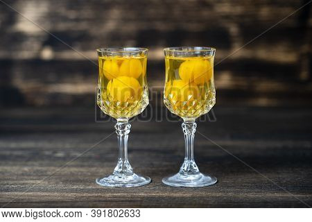 Homemade Tincture Of Yellow Cherry Plum In A Two Wine Crystal Glass On Wooden Background, Ukraine
