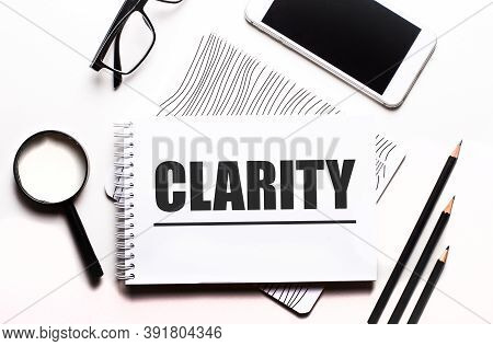 On A White Background Glasses, A Magnifier, Pencils, A Smartphone And A Notebook With The Text Clari