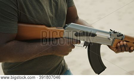 Violent Man Aiming With Assault Rifle While Walking In Desert Area. High Quality Photo