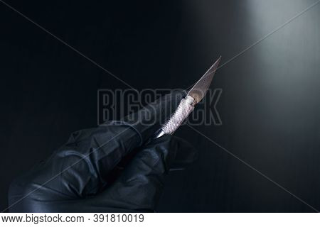 Scalpel In Hand In Glove Isolated On Black Background