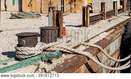 Mooring Ropes Tied On A Rusty Steel Bollard On A Deck. Ships Secure Moored On An Old Industrial Harb
