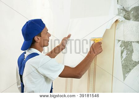 One painter worker peeling off wallpaper during interior home repair renovation work