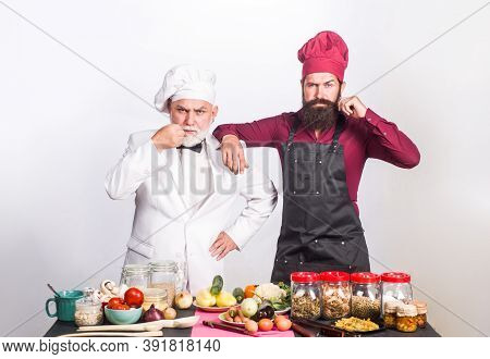 Kitchen. Cooking. Two Chefs On Kitchen. Serious Beared Chef Man. Delicious Food. Male Chef In Unifor