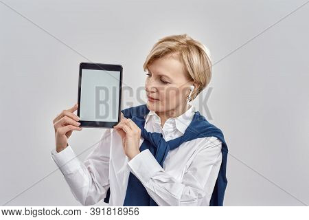 Portrait Of Elegant Middle Aged Caucasian Woman Wearing Business Attire Holding, Looking At Tablet P