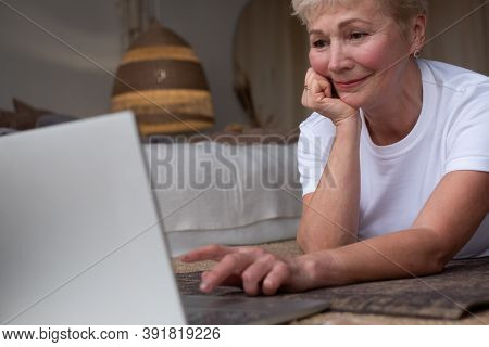 Active Senior Woman Surfing In Internet On Yoga Mat.