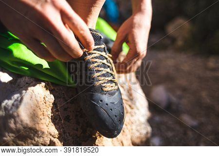 Rock Climber Puts On Climbing Shoes And Ties Shoelaces. A Girl Sits On A Stone And Puts On Climbing