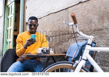 Black Tourist Man Using Cellphone Sitting In In A Cafe.