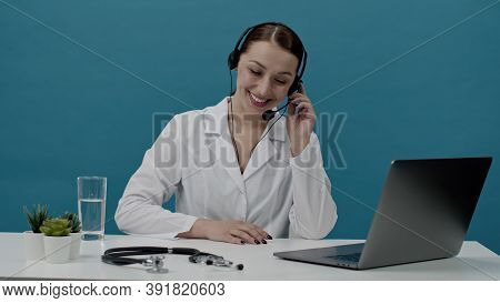 Beautiful Positive Doctor In White Coat And Headphones Talking On Phone, Specialist Of Call Center R