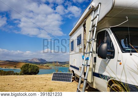 Camping On Nature. Camper Vehicle With Portable Ladder And Solar Panel. Caravanning Equipment, Maint