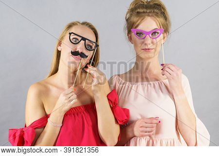 Happy Two Women Holding Paper Decoration Photo Booth Mask Glasses And Moustache On Stick, Having Fun