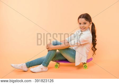 Girl Ride Penny Board Yellow Background. Kid Having Fun With Penny Board. Hobby Favorite Activity. C