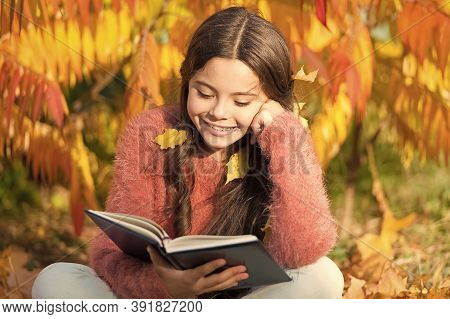 Her Hobby Is Reading. Cute Small Child Reading Book On Autumn Day. Adorable Little Girl Enjoy Englis