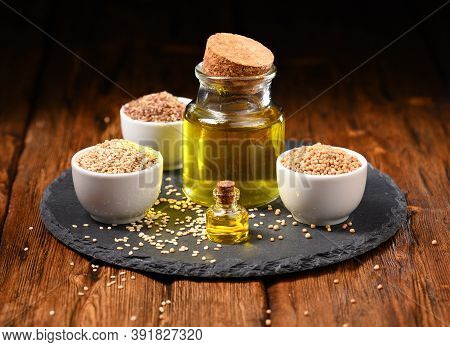 Sesame Oil, Sesame Seeds And Mustard Seeds On The Slate Plate.