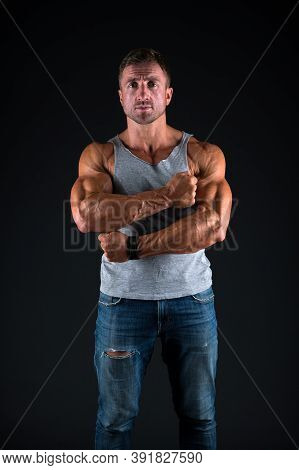 Athletic Man Cross Strong Muscular Arms With Biceps Triceps Muscles In Casual Wear Black Background,