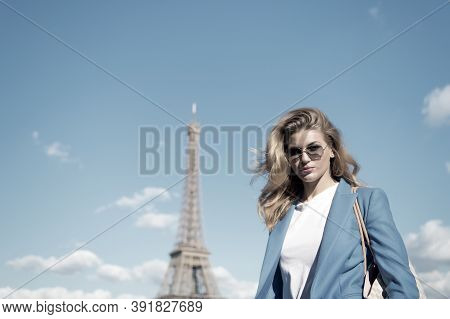Woman At Eiffel Tower In Paris, France On Blue Sky. Girl Traveler In Sunglasses, Jacket On Sunny Sum