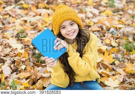 Born To Read. Happy Child Hold Book Sitting On Autumn Leaves. School Library. Reading And Literacy E