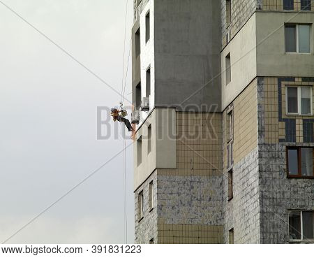 Warming An Old Multi-storey Building With Expanded Polystyrene Plates. A Worker On Ropes Plastering