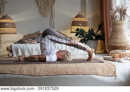 Sporty Senior Woman Doing Halasana, Plough Pose Or Yin Yoga Snail Posture